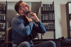 Portrait d'un mâle élégant qui lui-même rasant dans un salon de coiffure image stock