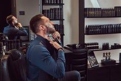 Portrait d'un mâle élégant qui lui-même rasant dans un salon de coiffure photo libre de droits