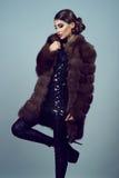 Portrait d'un manteau noir brillant de port de robe et de sable de beau modèle fascinant photographie stock