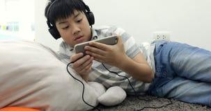 Portrait d'un mensonge de la préadolescence asiatique heureux de garçon éveillé avec le téléphone et les écouteurs intelligents e clips vidéos