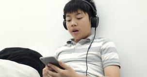 Portrait d'un mensonge de la préadolescence asiatique heureux de garçon éveillé avec le téléphone et les écouteurs intelligents e banque de vidéos