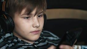 Portrait d'un mensonge heureux d'adolescent éveillé avec le smartphone et les écouteurs et d'écouter la musique à la maison Enfan banque de vidéos