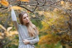Portrait d'un modèle de fille qui se tient parmi les arbres, avec un h Image stock