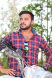 Portrait d'un modèle de jeune homme se reposant sur un vélo dans la forêt photos stock