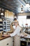 Portrait d'un négociant supérieur d'épice se tenant au compteur dans le magasin photos libres de droits