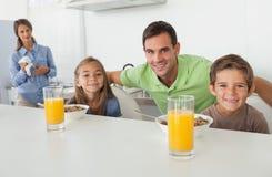 Portrait d'un père et de ses enfants prenant le petit déjeuner Images stock