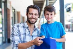 Portrait d'un père et de son fils ouvrant un sac Photo stock