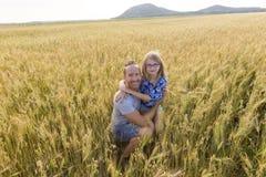 Portrait d'un père et d'une fille jouant dans le domaine de blé au coucher du soleil Image libre de droits