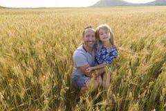 Portrait d'un père et d'une fille jouant dans le domaine de blé au coucher du soleil Photographie stock libre de droits