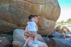 Portrait d'un père portant son fils s'asseyant sur une roche, Koh Li photo stock