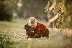 Portrait d'un petit garçon avec le petit chien en parc Images stock