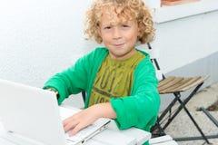 Portrait d'un petit garçon blond à l'aide d'un ordinateur portable Photo stock