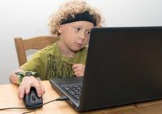 Portrait d'un petit garçon blond à l'aide d'un ordinateur portable Image libre de droits