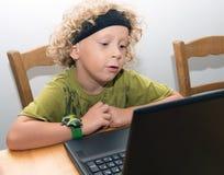 Portrait d'un petit garçon blond à l'aide d'un ordinateur portable Image stock