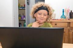 Portrait d'un petit garçon blond à l'aide d'un ordinateur portable Photo libre de droits