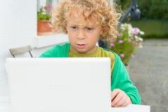 Portrait d'un petit garçon blond à l'aide d'un ordinateur portable Photos stock