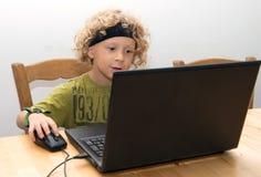 Portrait d'un petit garçon blond à l'aide d'un ordinateur portable Photographie stock