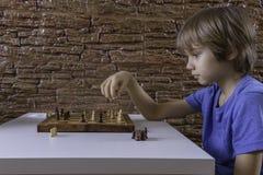 Portrait d'un petit garçon caucasien jouant des échecs et faisant la prochaine étape images stock
