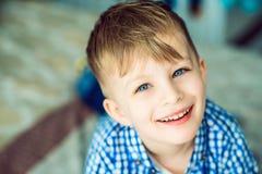 Portrait d'un petit garçon de sourire aux yeux bleus se trouvant sur le lit de ses parents Images stock