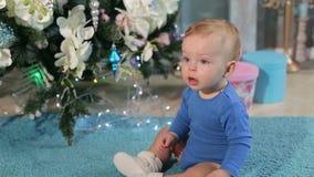 Portrait d'un petit garçon mignon près d'un arbre de Noël décoré banque de vidéos