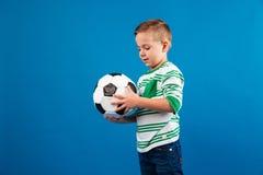 Portrait d'un peu d'enfant regardant et tenant le ballon de football Images libres de droits