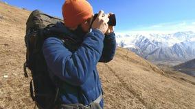 Portrait d'un photographe barbu heureux de voyageur dans les lunettes de soleil et un chapeau avec une cam?ra r?flexe dans ses ma banque de vidéos