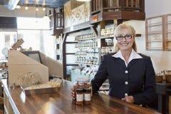 Portrait d'un propriétaire féminin heureux se tenant au compteur avec le pot d'épice dans le magasin images libres de droits