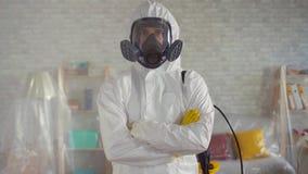 Portrait d'un scientifique masculin dans un masque protecteur et une salopette blanche, croisant ses bras posant pour la caméra clips vidéos