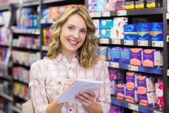 Portrait d'un sourire écriture assez blonde de femme sur un bloc-notes Image stock