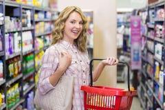 Portrait d'un sourire achat assez blond de femme produits avec un panier à provisions Image libre de droits