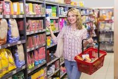 Portrait d'un sourire femme assez blonde ayant un produit dans des ses mains Photos stock