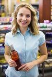 Portrait d'un sourire femme assez blonde ayant une bouteille de bloc-notes et de vin dans des ses mains Photo stock