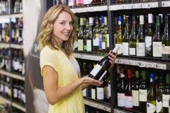 Portrait d'un sourire femme assez blonde ayant une bouteille de vin dans des ses mains Photos libres de droits