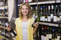 Portrait d'un sourire femme assez blonde ayant une bouteille de vin dans des ses mains Photographie stock