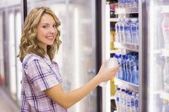 Portrait d'un sourire femme assez blonde prenant une bouteille d'eau Photos stock