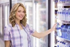 Portrait d'un sourire femme assez blonde prenant une bouteille d'eau Images libres de droits