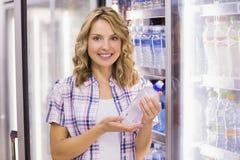 Portrait d'un sourire femme assez blonde prenant une bouteille d'eau Photo stock