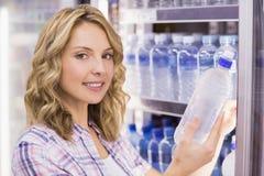 Portrait d'un sourire femme assez blonde prenant une bouteille d'eau Photographie stock
