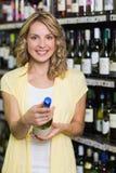 Portrait d'un sourire femme assez blonde regardant la bouteille de vin Photos libres de droits