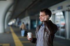 Portrait d'un support beau de jeune homme près vol de attente d'aéroport du prochain et de parler au téléphone portable Photo libre de droits