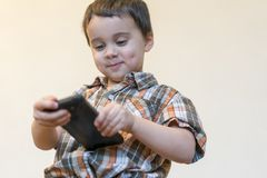 Portrait d'un t?l?phone portable de sourire de participation de petit gar?on d'isolement au-dessus du fond clair enfant mignon jo image libre de droits