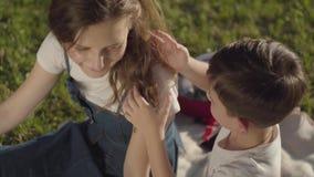 Portrait d'un temps plus ancien de dépense de soeur avec le jeune frère dehors Le garçon touchant des cheveux de la fille en parc clips vidéos
