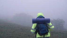 Portrait d'un touriste d'homme dans un gilet de signal dans un capot avec un sac à dos marchant dans la vue arrière de brouillard banque de vidéos