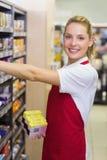 Portrait d'un travailleur blond de sourire prenant un produit dans l'étagère Image libre de droits