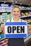 Portrait d'un travailleur blond de sourire tenant un signe Photos stock