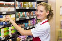 Portrait d'un travailleur de sourire prenant un produit dans l'étagère Photographie stock libre de droits