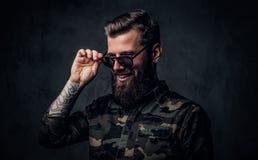 Portrait d'un type barbu élégant avec les mains tatouées dans la main militaire de participation de chemise sur des lunettes de s photo stock