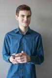 Portrait d'un type beau regardant dans l'appareil-photo avec un téléphone dans sa main Dans une chemise verte Brunette avec les y Photos libres de droits