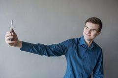 Portrait d'un type beau regardant dans l'appareil-photo avec un téléphone dans sa main Le type fait la photo d'individu Dans une  Images stock