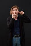 Portrait d'un type drôle avec le doigt dans son nez et oreille sur le fond noir photo libre de droits